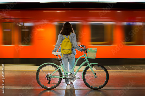 Fototapeta Teenager girl in jeans with yellow backpack and bike standing on metro station, waiting for train, smiling, laughing. Orange train passing by behind the girl. Futuristic subway station. Finland, Espoo obraz