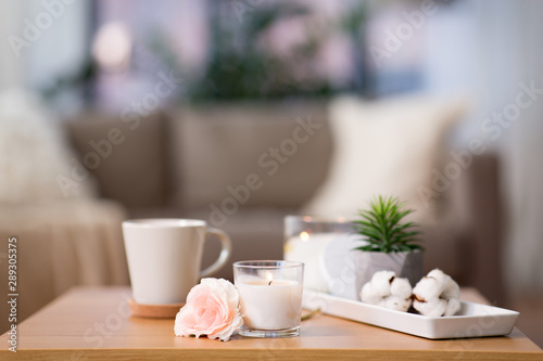 Printed kitchen splashbacks Amsterdam decoration, hygge and cosiness concept - burning fragrance candle and flower bunch on wooden table
