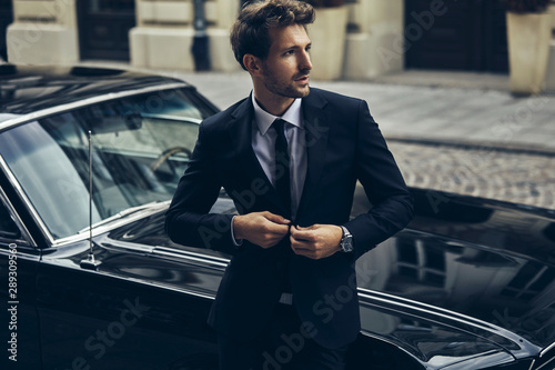 Obraz na plátně Handsome man in black suit with old classic car