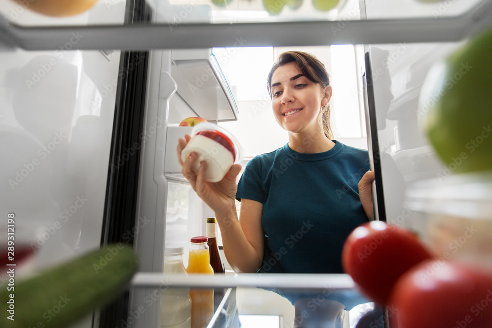 Fototapeta healthy eating, food and diet concept - happy woman taking yoghurt from fridge at home kitchen