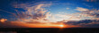 canvas print picture - Wide panorama of sunset sky with clouds and sunlight over farm