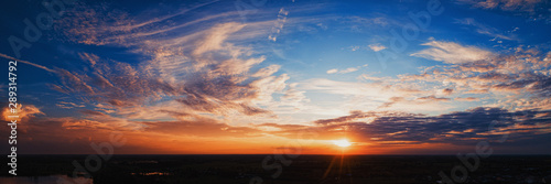 Wide panorama of sunset sky with clouds and sunlight over farm - 289314792