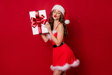 Pretty Lady Holding Big Giftbox In Hands Sending Air Kiss To Handsome Santa Wear Fluffy Mini Dress Isolated Red Background