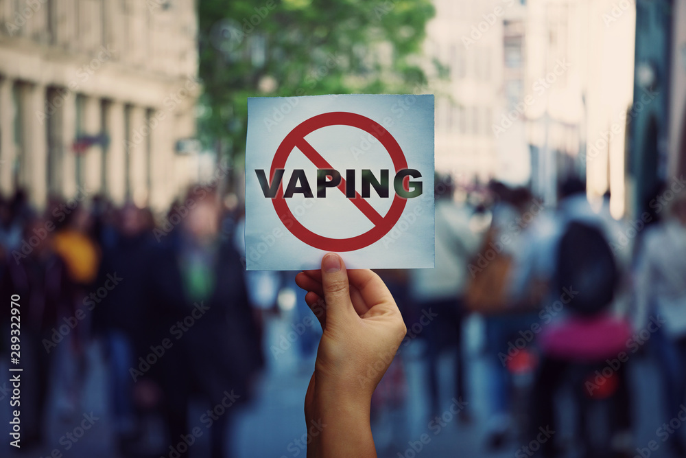 Fototapeta Human hand holding a protest banner stop vaping message over a crowded street background. Banning flavored vaping products to discourage people from smoking electronic cigarettes. Health risk concept.