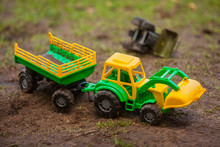 The Toy Tractor Is Working. Green And Yellow Tractor With A Trailer. Tractor With A Bucket, Toy.