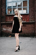 Leinwanddruck Bild - Young blond woman with long hair in a black dress near a brick red wall. Stylish girl in the city.