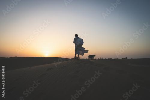 Fotografering  uomo nel deserto al tramonto