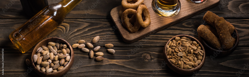 Fototapeta panoramic shot of bottle of light beer near bowls with snacks on wooden table