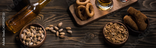 panoramic shot of bottle of light beer near bowls with snacks on wooden table Wallpaper Mural