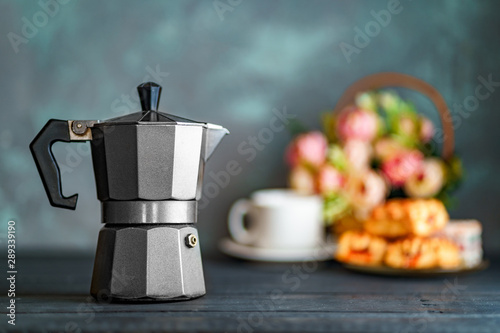 Obraz na plátně  Mocha coffee maker, flowers and sweets on dark background for coffee time