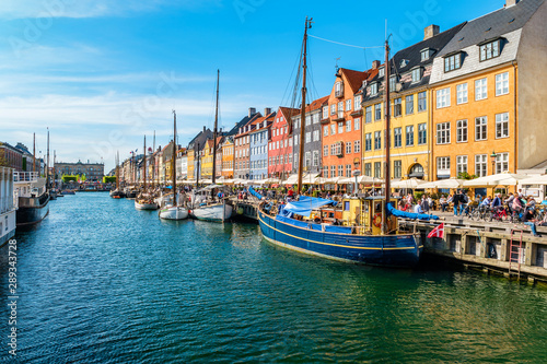 View of Nyhavn pier with color buildings, ships, yachts and other boats in the Old Town of Copenhagen, Denmark