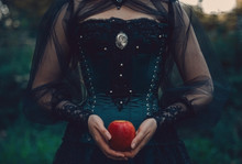 Woman In Green Victorian Costume Holds Red Apple