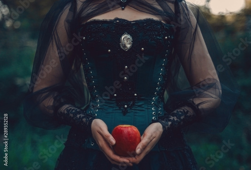 woman in green victorian costume holds red apple Fototapeta