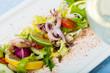 Leinwanddruck Bild Tasty salad of boiled squids, lemon and lettuce leaves at plate