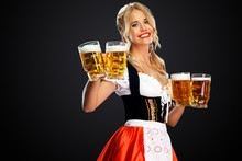 Young Sexy Oktoberfest Girl Waitress, Wearing A Traditional Bavarian Or German Dirndl, Serving Two Big Beer Mugs With Drink Isolated On Black Background.
