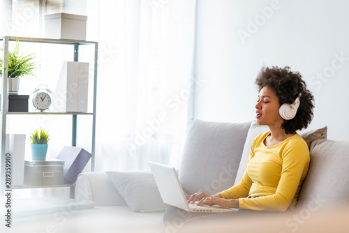 Young beautiful african american woman relaxing and listening to music using headphones. Smiling young woman watching a video with her laptop while siting on a sofa - 289359980