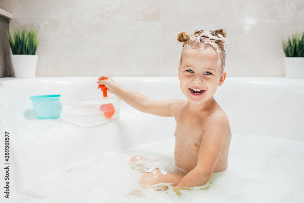 Fototapety, obrazy: Bath time is fun. Selective focus image of a cute little girl taking a bath and playing with toys while sitting in a luxurious bathtub