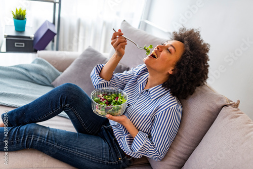Fotografija Cheerful young afro american woman eating vegetable salad at home