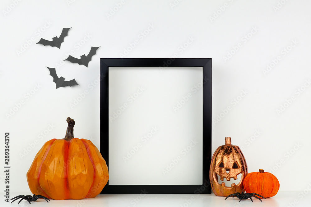 Fototapety, obrazy: Mock up black frame with Jack o Lantern and pumpkin decor on a shelf or desk. Halloween concept. Portrait frame against a white wall with bats.
