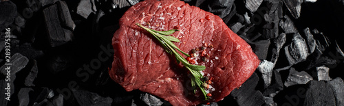 panoramic shot of raw beef sirloin with rosemary, salt and pepper on coal pieces