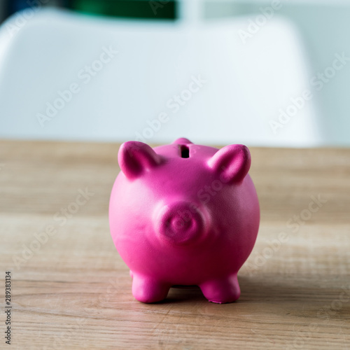 close up of pink piggy bank on wooden desk in office