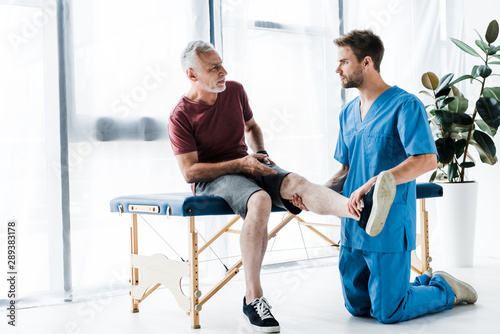 handsome doctor touching leg and looking at mature patient