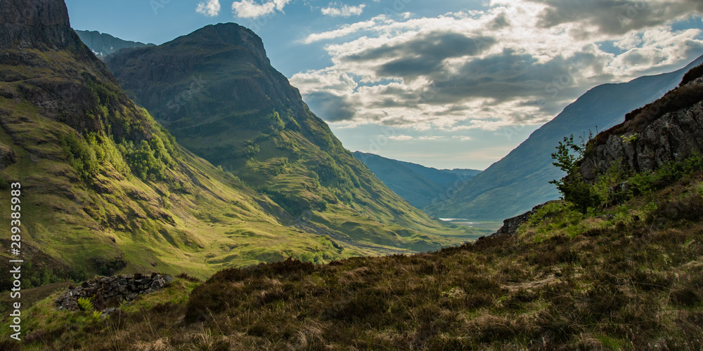 Fototapeta View of valley in Glencoe Scotland in morning with shadows and road snaking through to lake in distance