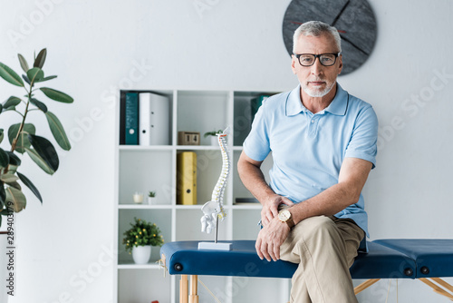 Fototapety, obrazy: bearded man in glasses sitting on massage table near spine model