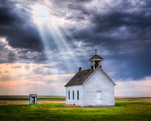 Old Rural Church At Sunset With Sunrays Beaming Down From The Sky