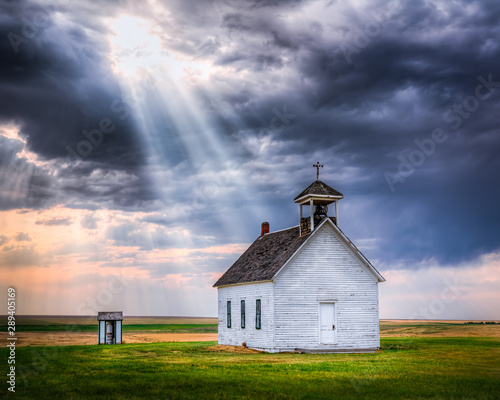 Old Rural Church at Sunset with Sunrays Beaming Down From the Sky Fototapet