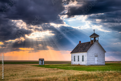 Stampa su Tela  Old Rural Church at Sunset with Sunrays Beaming Down From the Sky