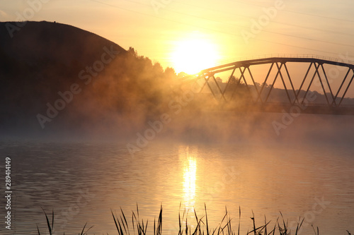 Poster Cappuccino sunrise on the background of the bridge over the misty river