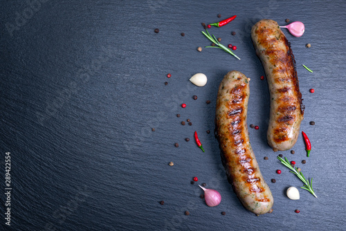 Fotografia top view of grilled sausages decorated with chili and dry pepper, garlic, rosema
