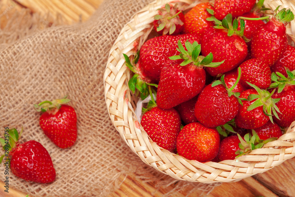 Fototapety, obrazy: Basket of strawberry harvest on wooden table close up