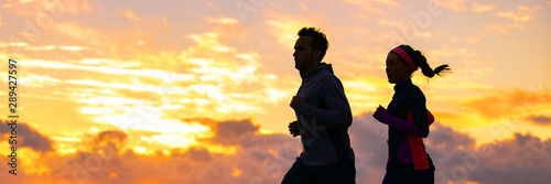 plakat Run fit couple sport banner panorama of runners friends woman and man training cardio together running on outdoor race at sunset panoramic background. Silhouettes of two athletes working out.