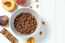 Top View On Fresh Chocolate Granola In Grey Bowl With Figs, Peach On White Wooden Background. Copy Space. Healthy And Tasty Breakfast. Vegan Food. Food Photo Background