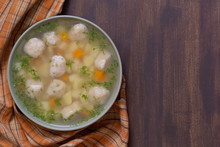 Top View Of Soup In Bowl With Dumplings On Wooden Background