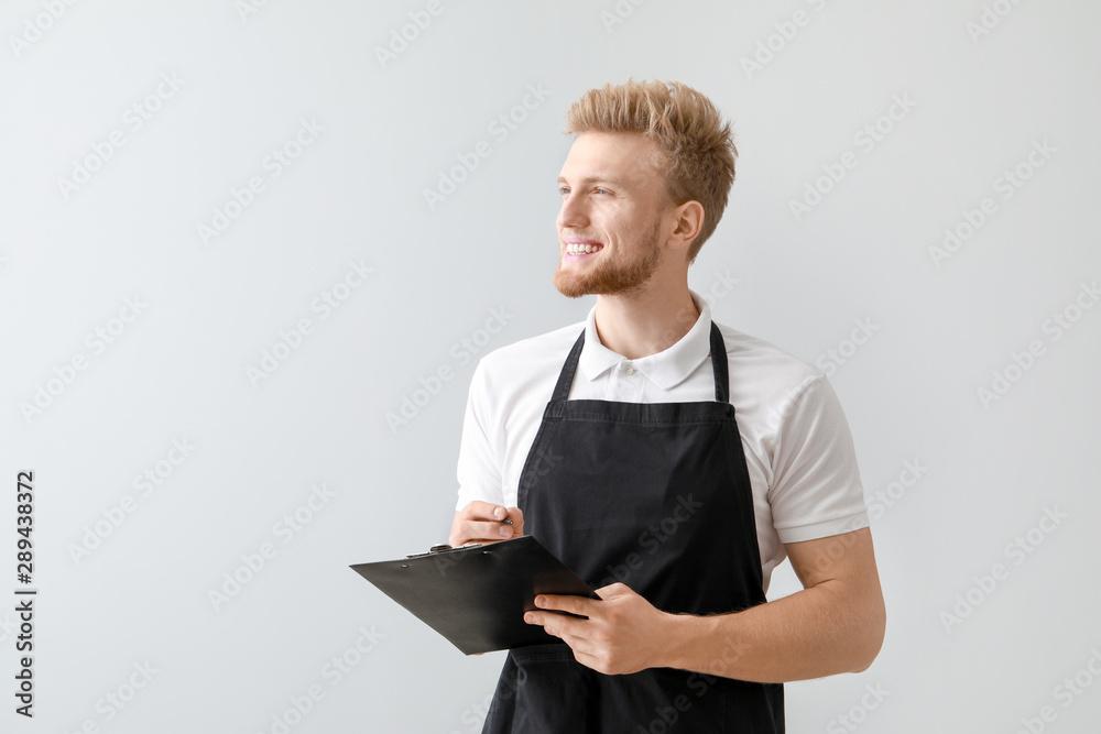 Fototapeta Handsome waiter with clipboard on light background