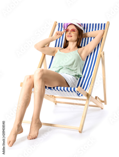 Fototapeta Beautiful young woman relaxing on sun lounger against white background