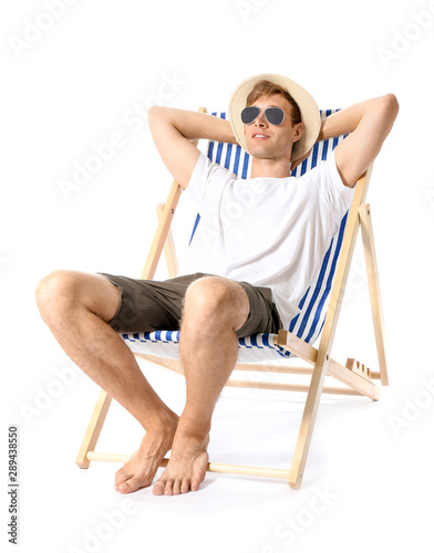 Fotografie, Obraz Young man relaxing on sun lounger against white background