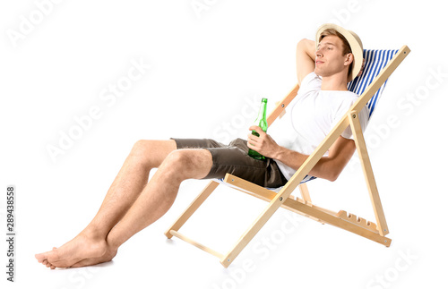 Fotografia, Obraz Young man relaxing on sun lounger against white background