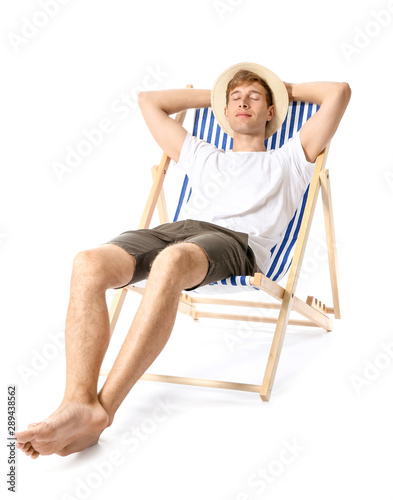Fototapeta Young man relaxing on sun lounger against white background