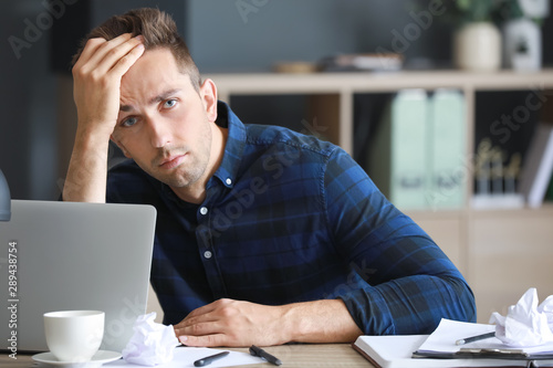 Valokuvatapetti Stressed young man at table in office