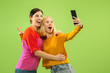 Leinwanddruck Bild - Portrait of pretty charming girls in casual outfits isolated on green studio background. Girlfriends or lesbians making selfie. Concept of LGBT, equality, human emotions, love, relation.