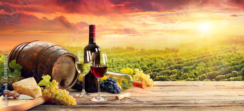 Keuken foto achterwand Alcohol Barrel Wineglasses Cheese And Bottle In Vineyard At Sunset