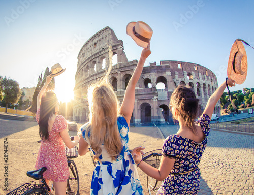 Photo Three happy young women friends tourists with bikes waving hats at Colosseum in Rome, Italy at sunrise