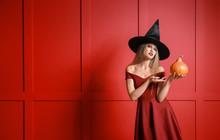 Beautiful Woman Dressed As Witch For Halloween On Color Background