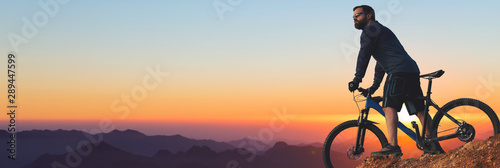 Fototapeta Cyclist in shorts and jersey on a modern carbon hardtail bike with an air suspension fork rides off-road on the orange-red hills at sunset evening in summer obraz