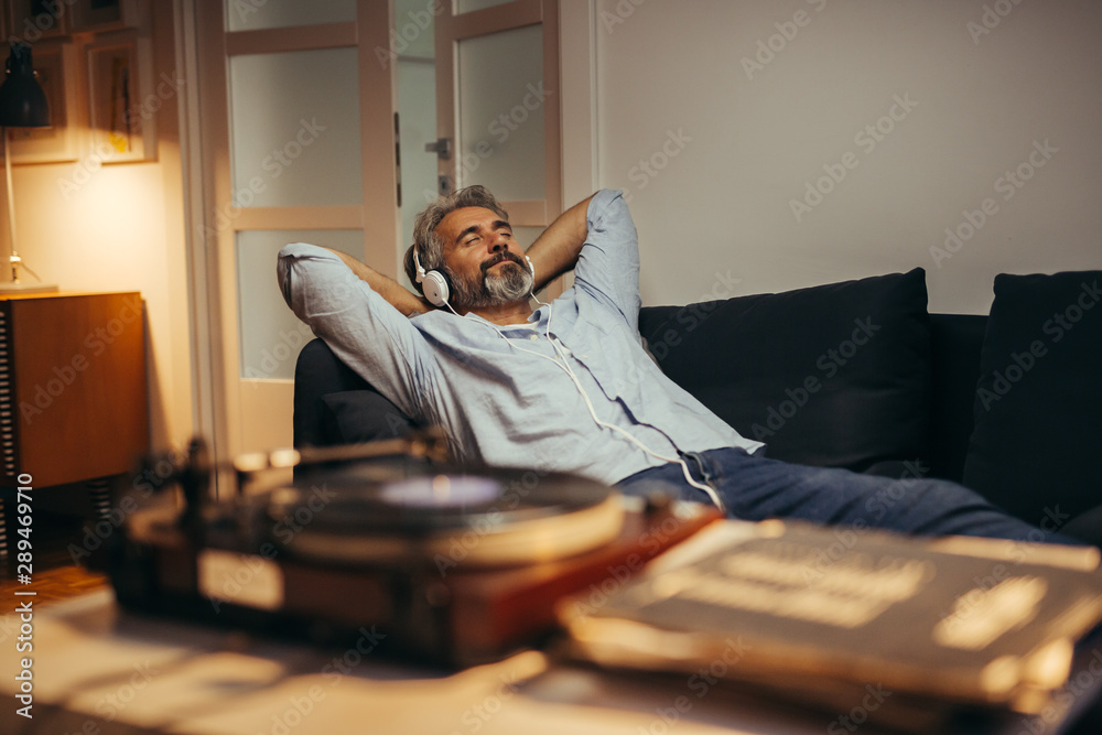 Fototapeta mid aged man listening music with headphones on record player, relaxed in sofa at his home