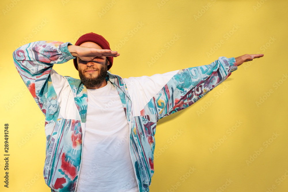 Fototapeta Stylish young hipster man with beard in red hat and a retro jacket of 90s on yellow background.Crazy hipster guy emotions. Collage in magazine style